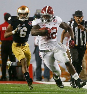 Alabama running back Eddie Lacy pulls away from Notre Dame's KeiVarae Russell during the second half of Monday night's BCS National Championship Game. Lacy led Alabama with 20 rushes for 140 yards, including a 20-yard touchdown run. He also caught an 11-yard touchdown pass from quarterback AJ McCarron. Lacy had more rushes than the entire Notre Dame team.
