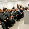 Members of the Benton County Sheriff's Office listen as Tim Keck speaks. Keck is a former Rogers pol...