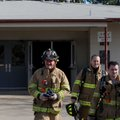 Firefighters leave a building after completing their smoke investigation Monday at 4 North Double Sp...