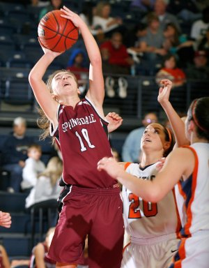 Brittany Jurgens, left, a Springdale senior, attempts a shot under the basket against Rogers Heritage during the second half on Tuesday at Rogers Heritage.