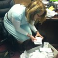 Mary Ley, communications director for the Bentonville School District, looks through survey results ...