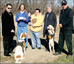 Holly Beeman (second from left) presented at check for $1,205 to Gentry Mayor Kevin Johnston (left) to pay for heat lamps in each of the 10 kennel areas at the Gentry dog impoundment facility on Friday. Pictured with Johnston and Beeman are Tailwaggers treasurer Priscilla Dorado and nephew Dason Costa, secretary Laura Lewis, and Gentry animal control officer Skip Paczowski. Also pictured are two of the dozen or more dogs at the shelter awaiting adoption.