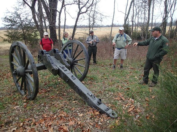 Hikers look over the chassis of a Civil War cannon replica.