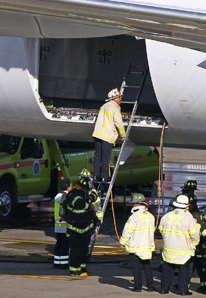 A Boston Fire Department chief looks into the cargo hold of a Japan Airlines Boeing 787 Dreamliner jet parked at a Terminal E gate at Logan International Airport in Boston, Monday, Jan. 7, 2013. A small electrical fire filled the cabin of the JAL aircraft with smoke Monday morning about 15 minutes after it landed in Boston. (AP Photo/Stephan Savoia)