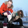 Amanda Mandras, right, sits next to her daughter, Tegan Mandras, 13, as they lace up their ice skate...