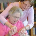 June Meunier of Fayetteville, right, a volunteer instructor, reaches Wednesday to help Nola Magee of...
