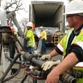 Daniel Kulberg, right, watches workers, including Ryan Albright, center, install liner to repair a s...