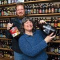 Duncan and Sharon McKinnon stand in front of their bottle collection Tuesday at their West Fork home...