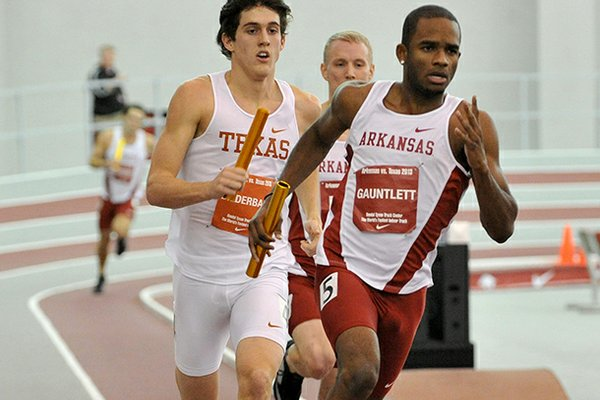 NWA Media/MICHAEL WOODS --01/11/2013-- Arkansas runner Akheem Gauntlett tries to keep the lead entering the final lap in the Mens 4x400 relay at the Randal Tyson Track Center in Fayetteville.