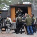 The Benton County Sheriff's Office SWAT team gears up to work a standoff Thursday on Hickory Lane in...