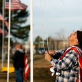 Maintence worker Marlin (cq) Johnson hoists an American flag outside the Benton County Memorial Park...