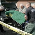 Greenland Police Chief Gary G. Ricker, left, helps Washington County personnel load the body of Bett...