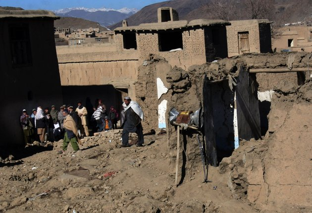 afghans-stand-near-a-damaged-mosque-following-an-explosion-in-sayedabad-wardak-southwest-of-kabul-afghanistan-sunday-jan-13-2013-an-explosion-killed-seven-afghan-villagers-sunday-as-they-tried-to-pull-bodies-of-insurgents-killed-from-the-rubble-of-a-village-mosque-after-a-night-raid-by-nato-and-afghan-troops-in-the-countrys-east-officials-said-four-insurgents-and-an-afghan-soldier-were-also-reported-to-have-been-killed