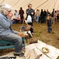 Longtime artist Maeve Courteau of Elkins, left, takes a break Saturday from making wooden spoons to ...