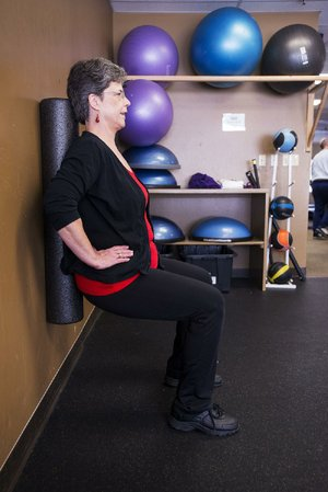 Linda Walker does a mostly isometric exercise, the wall squat, but adds the twist of trying to march her feet sideways without letting the foam roller get away from her — which is much harder than it looks.