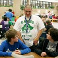 James Sandoval, Elmwood Middle School volunteer, talks Thursday with seventh-graders Eli Crawford an...