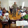 Syd Caldwell of Lowell leads the Sacred Harp Singers as they practice Sunday afternoon during their ...
