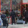 Rogers police officers, left, and an employee at Advance Auto Parts on Eighth Street in Rogers look ...