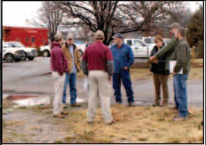 Representatives from the city of Gravette, the Arkansas Highway Department, a landscaping firm, and an engineering firm discuss a highway intersection beautification project in Gravette.
