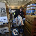 Barb Trusty, general manager for Kum & Go store No. 408, sorts through cases of beer Wednesday while...