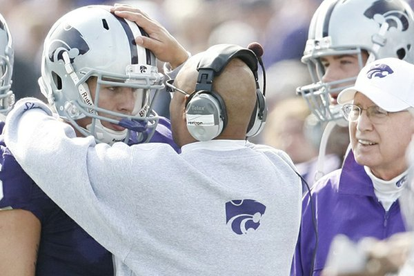 Wide receivers coach Michael Smith talks with Kansas State quarterback Grant Gregory on the sideline during a 2009 game against Colorado.