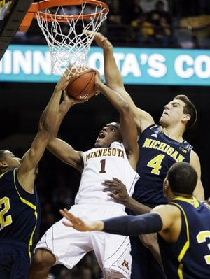Minnesota guard Andre Hollins (1) is fouled by Michigan forward Mitch McGary (4) as he tries to shoot in a crowd during the second half of Thursday's game in Minneapolis. Michigan won 83-75.