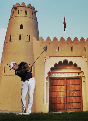 Jamie Donaldson of Wales tees off on the 15th hole in front of a poster of a castle during Thursday's ÿrst round of the European PGA Abu Dhabi Championship. Donaldson and Justin Rose are tied at 5-under-par 67 heading into today's second round in Abu Dhabi, United Arab Emirates.