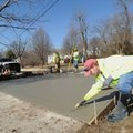 Brandon Williams with Fayetteville's Transportation Division, uses a trowel Thursday to smooth newly...