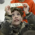 Gabriel Creasey, 9, checks out the $1 bill he received Friday while attending a program on saving mo...