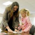 Kate Coleman, astronomy professor at NorthWest Arkansas Community College, helps Kira Baucom, 6, fol...