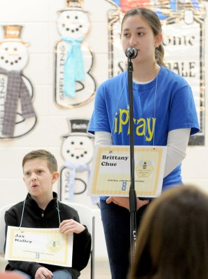 Jax Nally, left, of Young Elementary School reacts Friday as Central Junior High School's Brittany Chue spells the championship word correctly during the Springdale School District spelling bee at Parson Hills Elementary School. Jax was the first runner-up with Helen Tyson Middle School's Sojas Wagle as the second runner-up.