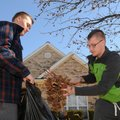 Zach Arrick, 16, left, holds a trash bag open as Cullen Arrick, 18, fills it with fallen gumballs fr...