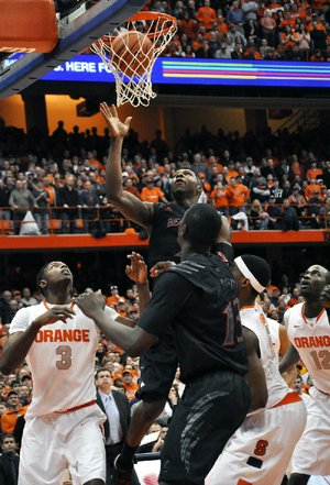 Cincinnati forward Titus Rubles (center) watches the ball go in for what proved to be the game-winner with 19.4 seconds left in Monday's game in Syracuse, N.Y. Syracuse forward C.J. Fair (lower right wearing a headband) was credited with the tip-in, even though he's not entirely sure he did it.
