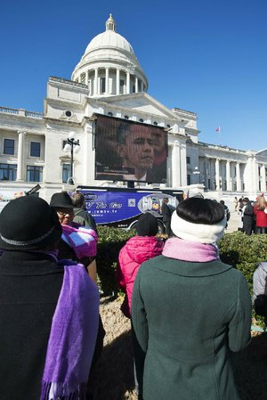 Spectators gather in front of the Arkansas State Capitol to watch President Barack Obama's ceremonial inauguration, which was supposed to be broadcast live on a jumbo TV monitor. Technical problems delayed the broadcast by at least 10 minutes.