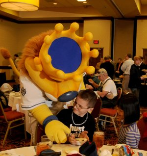 Lucas McDaniel, 10, of Springdale tries to keep Sluggerrr, the Kansas City Royals mascot, out of his ice cream Monday as Emily McDaniel, 9, watches during the 2013 Royals Caravan at the Springdale Rotary Club at the Holiday Inn in Springdale. The caravan featured former Royal Dennis Leonard and current players Bruce Chen, Danny Duffy and Will Smith. Royals owner David Glass also talked to members of the club and invited guests.