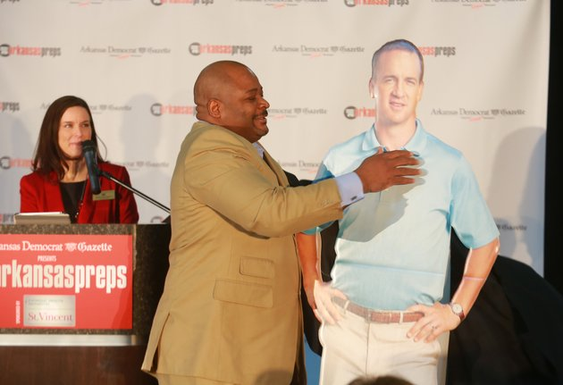 arkansas-democrat-gazette-events-manager-tabitha-cunningham-left-watches-as-keith-jackson-unveils-a-cutout-of-peyton-manning-who-will-be-the-keynote-speaker-of-the-all-arkansas-preps-awards-banquet