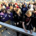 Parents, students and employees of the Elkins School District sign a steel beam Tuesday at a ceremon...