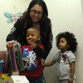 Kenneth Davis, 3, plays with one of the gifts he received Tuesday for being the 100,000th patient at...