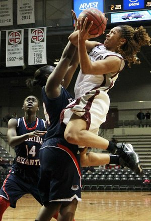 UALR junior guard Taylor Ford (right) shoots over Florida Atlantic defenders Latavia Dempsey (left) and Shanequa Schrouder during Wednesday's game at the Jack Stephens Center in Little Rock. Ford scored 16 points in the Trojans' 77-45 victory.