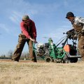 Kaleb Reynolds, left, and Kyle Anderson, both with the Springdale Parks department, use a sod cutter...