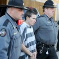 Zachary Holly, center, is escorted to a Benton County Sheriff's Office patrol car Nov. 28 after an b...