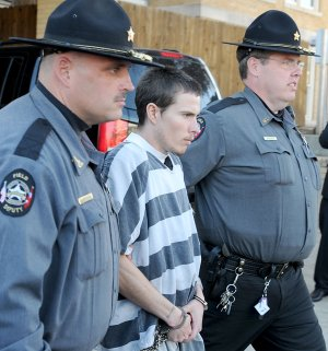 Zachary Holly, center, is escorted to a Benton County Sheriff's Office patrol car Nov. 28 after an bond hearing at the Benton County Courthouse in Bentonville.