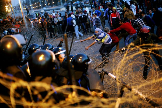 egyptian-protesters-pull-barbed-wires-during-a-protest-in-front-of-the-presidential-palace-in-cairo-egypt-friday-jan-25-2013