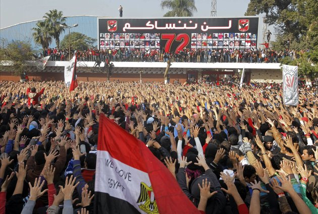 egyptian-soccer-fans-of-al-ahly-club-celebrate-a-court-verdict-that-returned-21-death-penalties-in-last-years-soccer-violence-inside-the-club-premises-in-cairo-egypt-saturday-jan-26-2013-egyptian-security-officials-say-military-to-deploy-in-port-said-after-at-least-8-people-died-in-the-mediterranean-city-of-port-said-after-a-judge-sentenced-21-people-to-death-in-connection-to-one-of-the-worlds-deadliest-incidents-of-soccer-violence-arabic-reads-we-will-never-forget-you