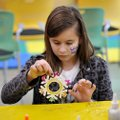 Chloe Sandoval, 9, from Fayetteville shakes the excess glitter off of her paper snowflake Saturday a...
