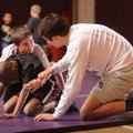 Coach Austin Riddle, right, helps instruct 9-year-old wrestlers Sam Lannutti, top, and Josh Cartwrig...