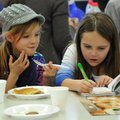 Aubrey Holloway, left, 8, and Megan Treacy, 8, both from Rogers, talk as they eat pancakes and read ...