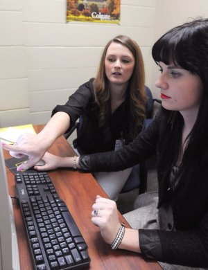 Rhiannon McKee (left), a mentor for the new Razor COACH program, helps Springdale Har-Ber senior Kayla Harmon, 18, fill out an online scholarship application Wednesday at the school. The program, developed through the University of Arkansas at Fayetteville and the Northwest Arkansas Council, is designed to help high school students overcome obstacles they face to get to college.