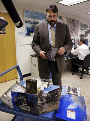 Joseph Kolly of the National Transportation Safety Board holds a burned battery case from the Japan Airlines Boeing 787 Dreamliner. The battery shows evidence of short-circuiting.