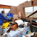 Volunteers, neighbors and emergency personnel work Tuesday, Jan. 29, 2013, to recover personal items...